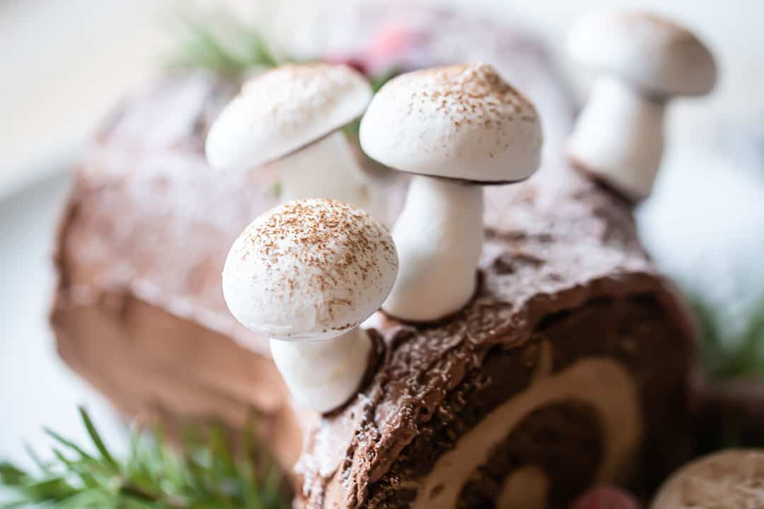 Close up image of meringue mushrooms on a chocolate yule log cake.