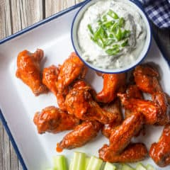 Chicken wings baked crispy & coated in spicy buffalo sauce, served on a tray with blue cheese dressing and celery sticks.