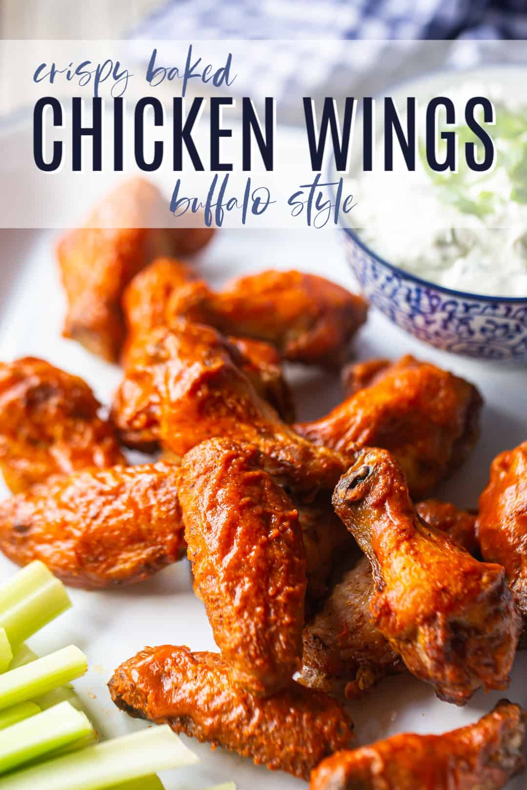 "Crispy baked chicken wings with spicy buffalo sauce, on a platter with celery sticks and blue cheese dip, with a text overlay above reading ""Crispy Baked Chicken Wings, Buffalo Style."""