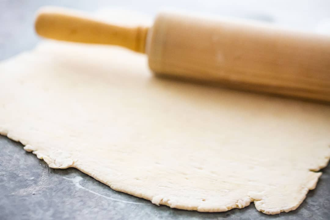 Rolling out puff pastry for pigs in a blanket.