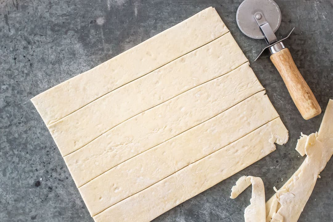 Cutting strips of puff pastry for pigs in a blanket.