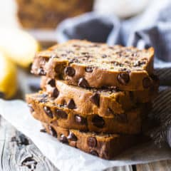 Chocolate chip banana bread slices stacked on a wood table with fresh bananas in the background.