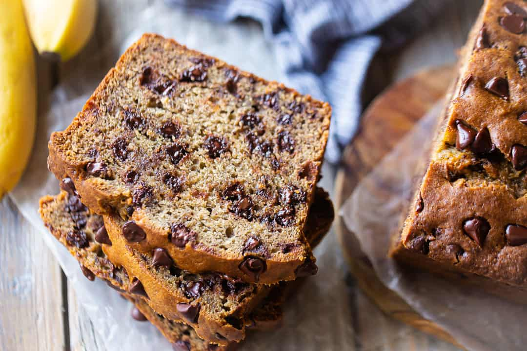 Chocolate chip banana bread sliced and served on a wooden board.