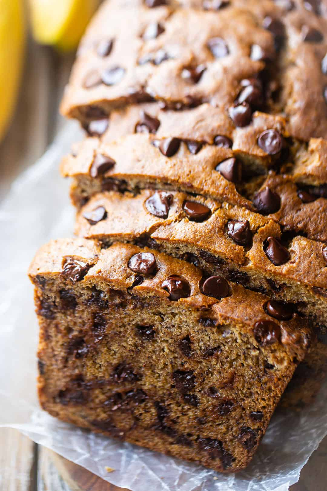 Banana bread recipe with chocolate chips, baked & sliced on a wood table with fresh bananas in the background.