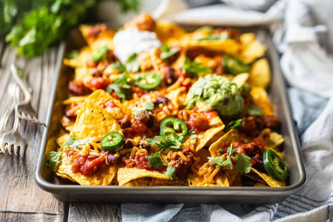 Homemade nachos recipe, prepared on a sheet pan with guacamole and sour cream.