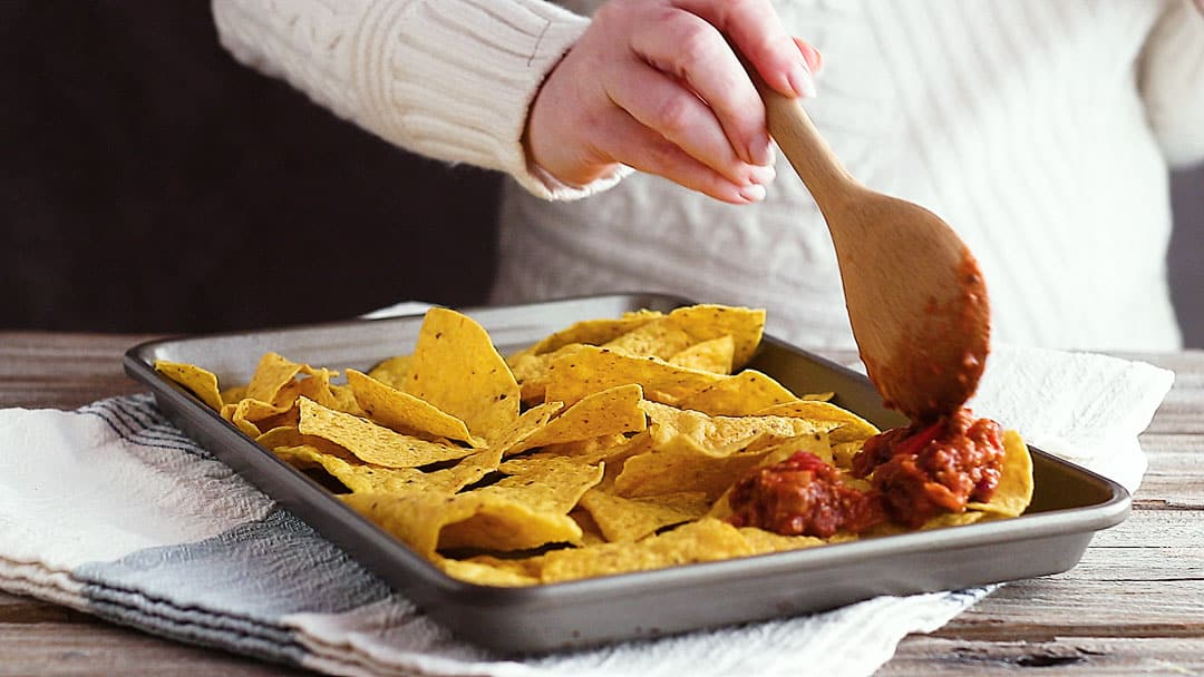 Spooning chili over tortilla chips for nachos recipe.