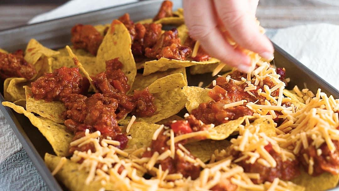 Sprinkling shredded cheese on sheet pan nachos recipe.