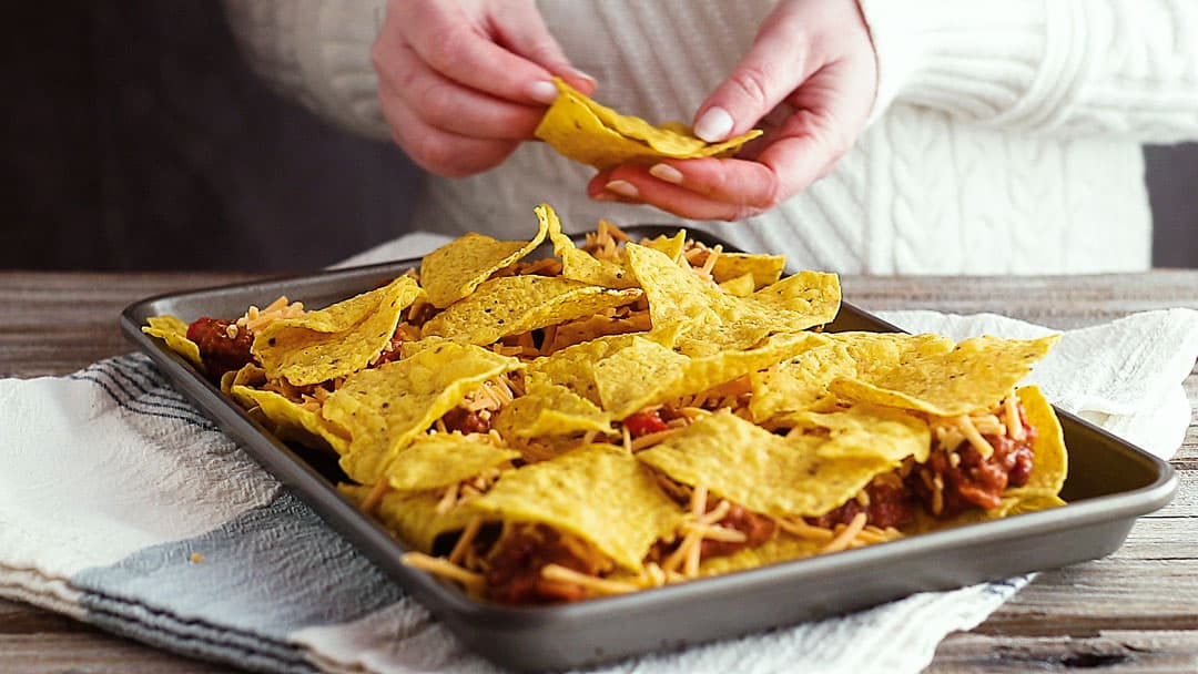 Adding a second layer of tortilla chips to nachos recipe.