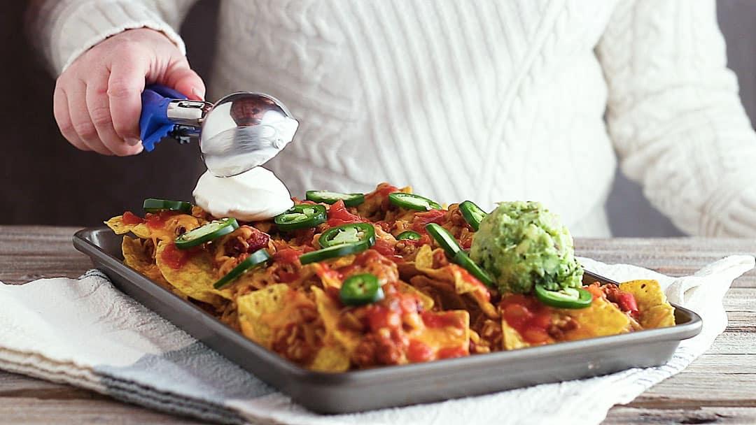 Topping sheet pan nachos with sour cream.
