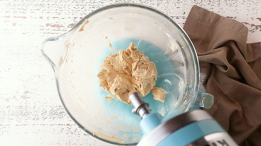 Adding egg to peanut butter blossoms dough.