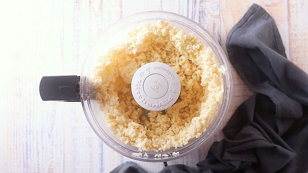 Sugar, salt, and butter in the bowl of a food processor.