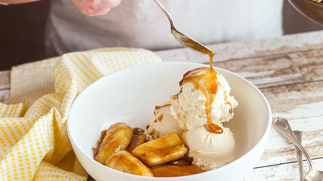 Drizzling bananas Foster over vanilla ice cream.