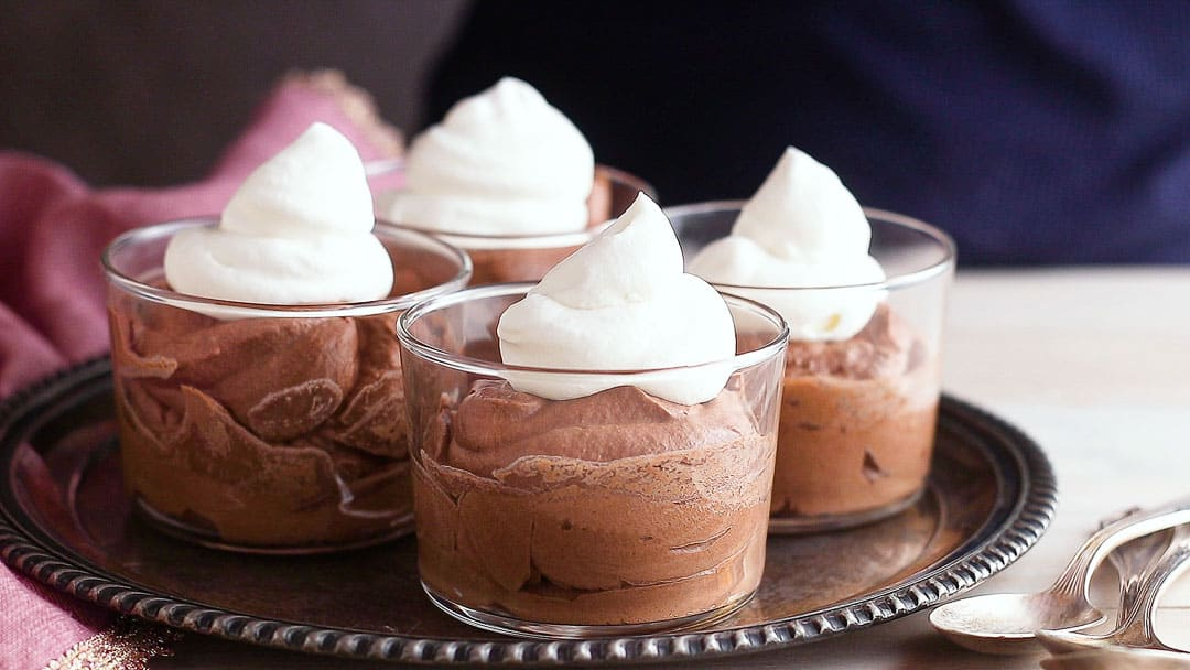 Topping chocolate mousse with whipped cream.