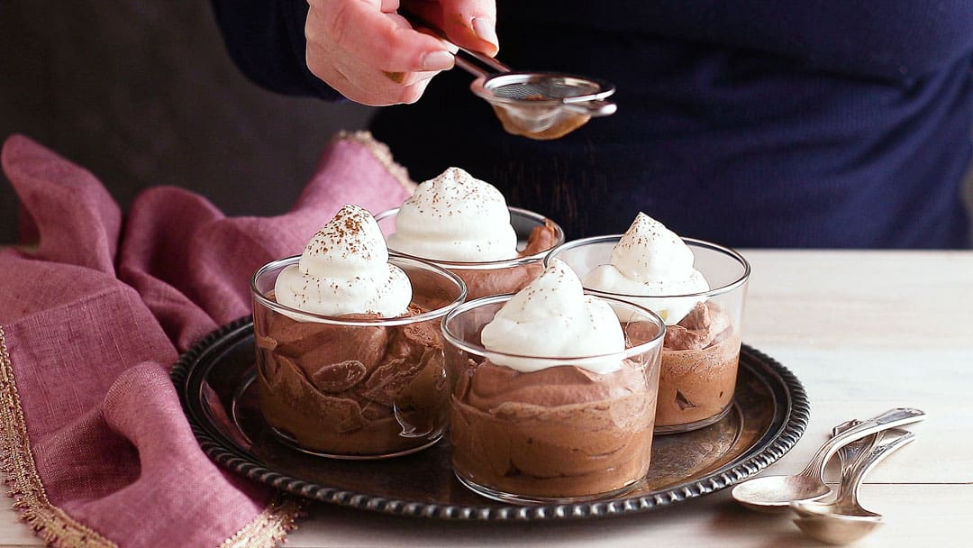 Garnishing chocolate mousse with cocoa powder.