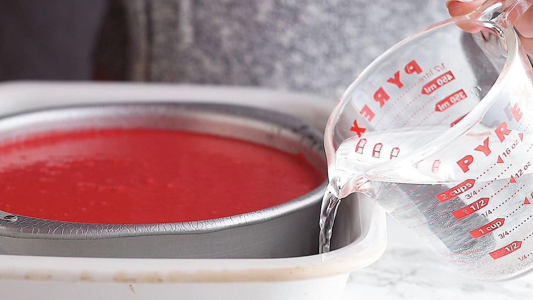 Creating a water bath in which to bake red velvet cheesecake.