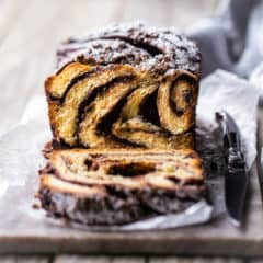 Chocolate babka on a cutting board with a knife.