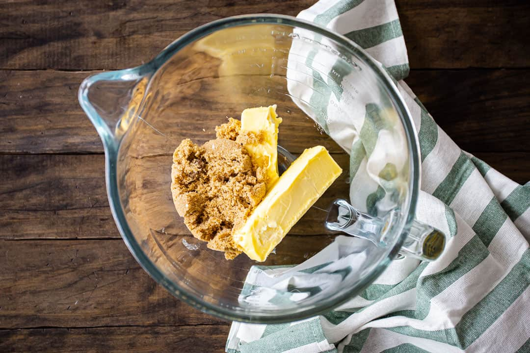 Irish butter and brown sugar in a large glass mixing bowl, on a dark wood tabletop.