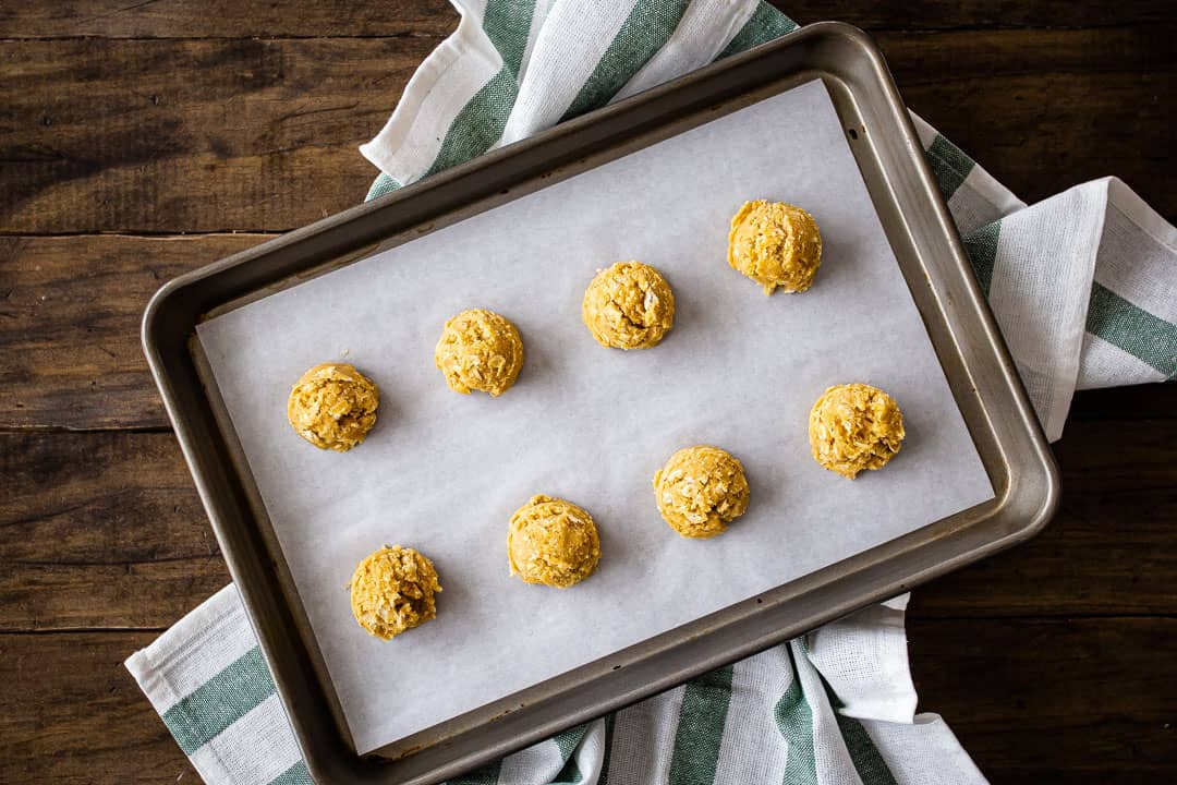 Scooping oatmeal cookie dough onto a parchment-lined baking sheet.