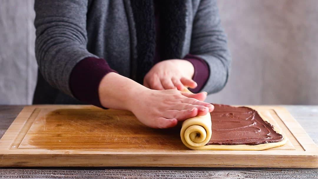 Rolling chocolate babka dough into a log.