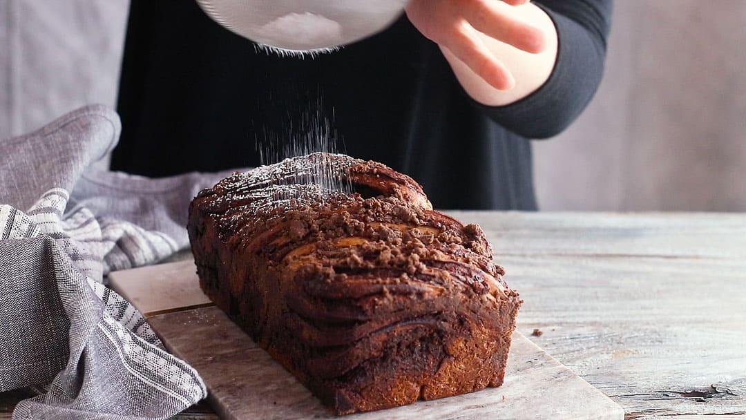 Dusting chocolate babka with powdered sugar.