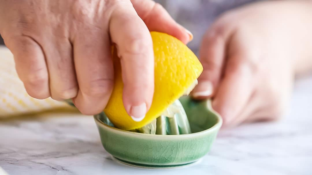 Juicing half a lemon with a small ceramic juicer.