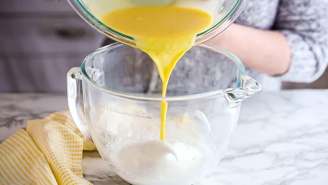 Adding lemon mixture to stiffly whipped egg whites.