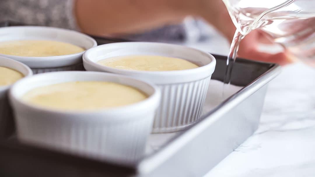 Creating a water bath to bake lemon pudding cakes.