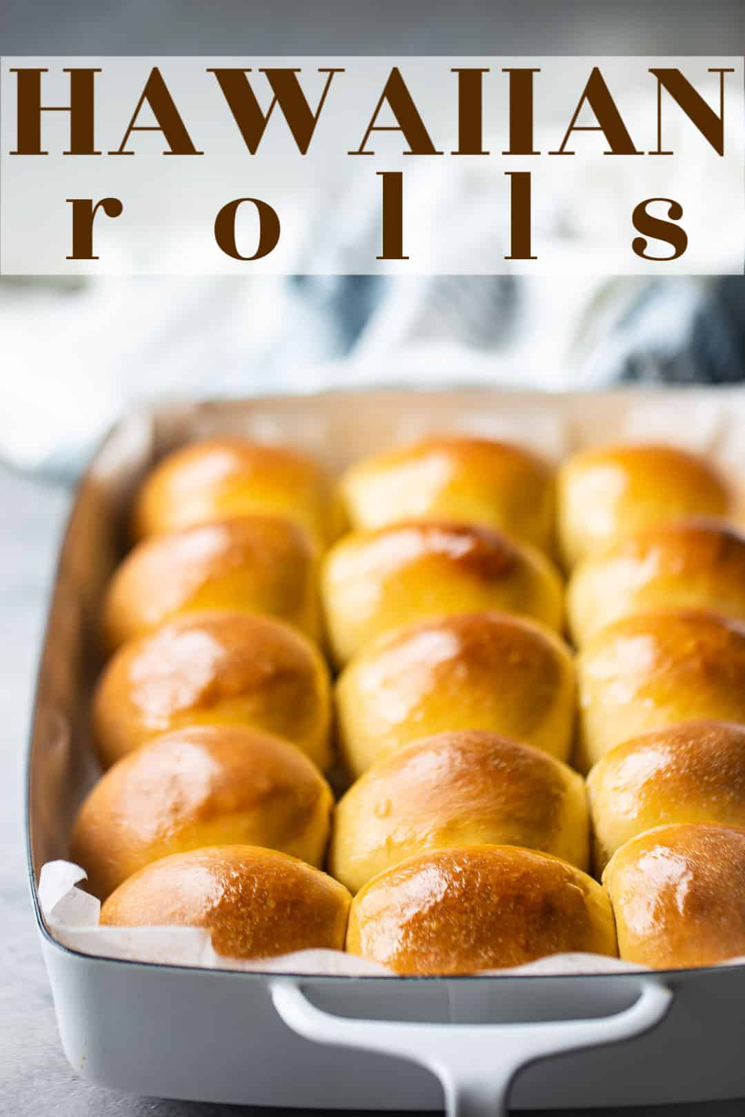 "Hawaiian roll sliders in a white enamel baking dish with a text overlay above that reads ""Hawaiian Rolls."""