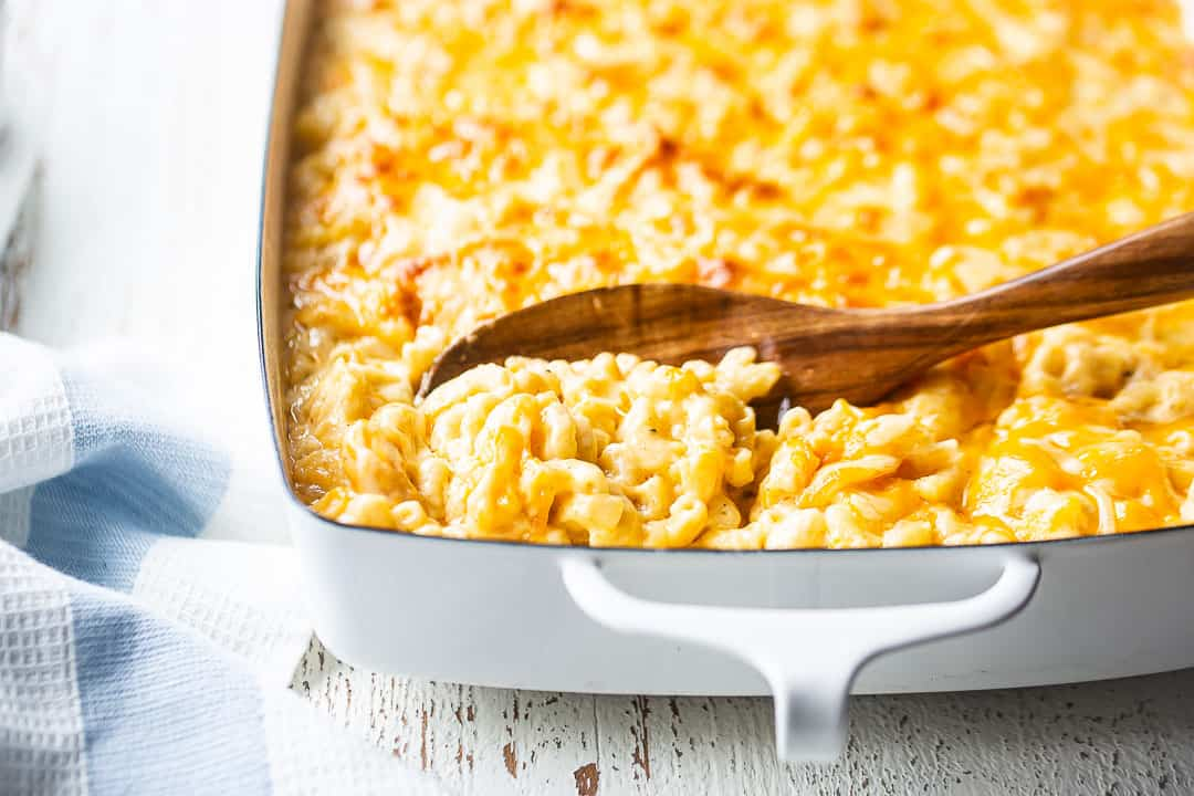 Homemade macaroni and cheese baked in a casserole dish, with a wooden serving spoon.