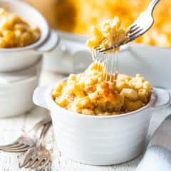 A fork pulling macaroni and cheese out of an individual ramekin, stretching the gooey cheese along with it.