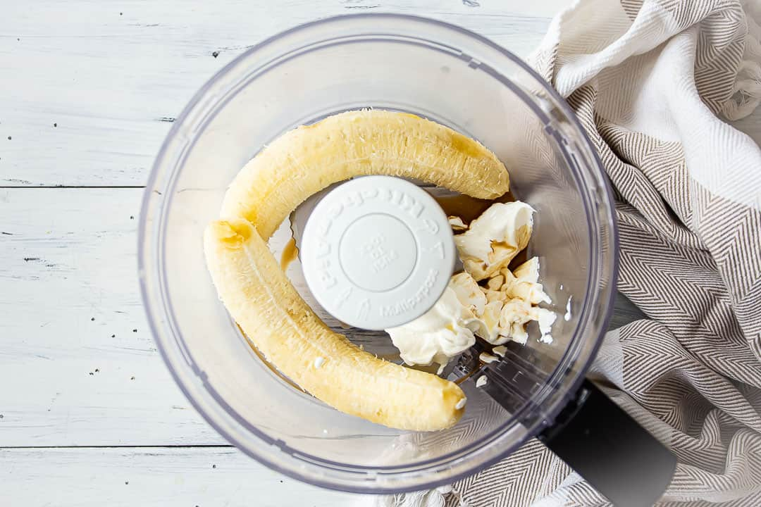 Bananas, sour cream, and vanilla in the bowl of a food processor.