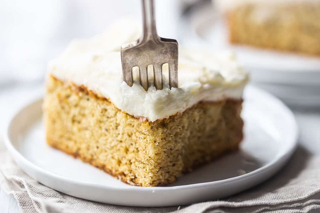 Banana cake with sour cream, topped with cream cheese frosting, with a vintage silver fork.