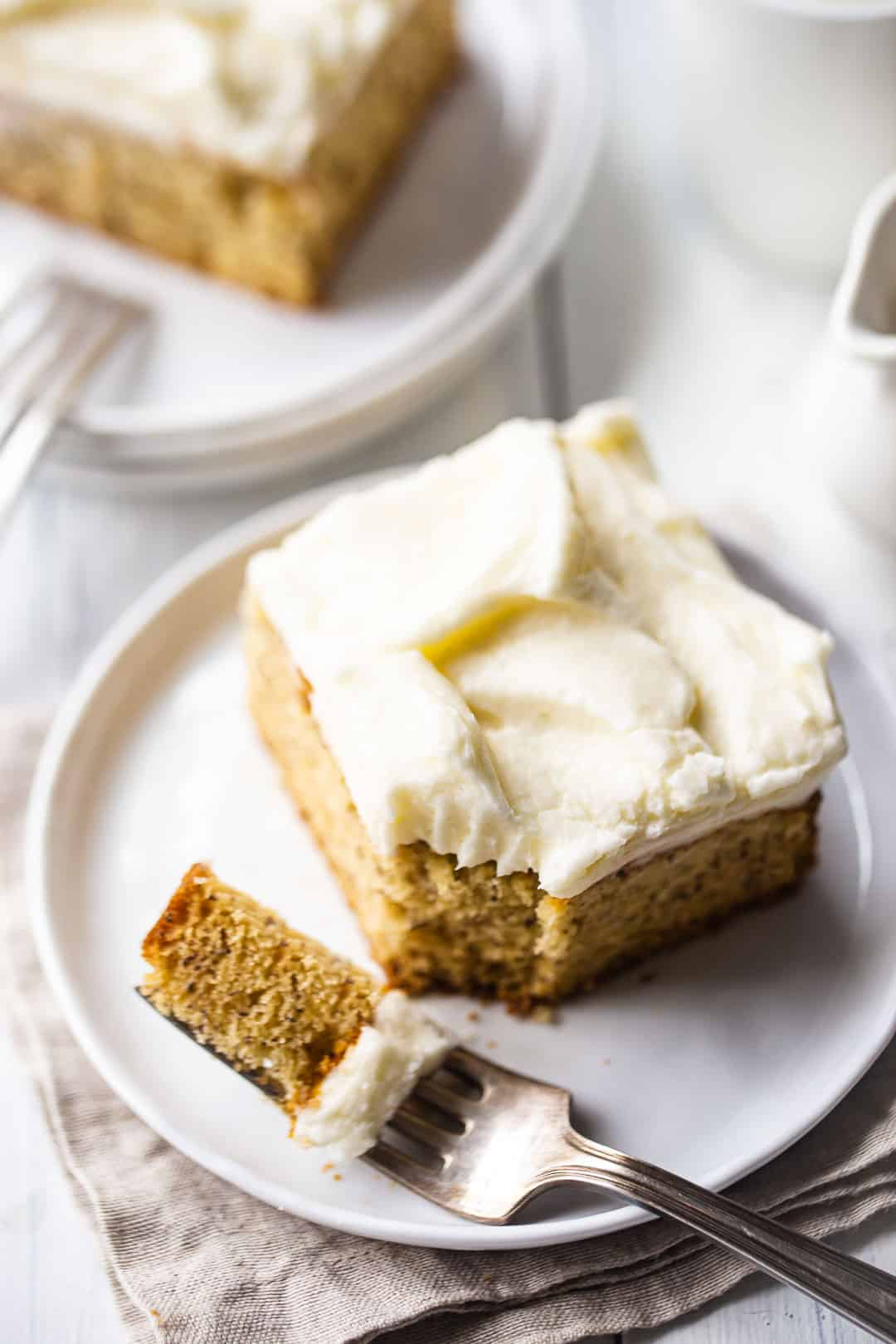 Moist banana cake cut into squares and served with cream cheese frosting.