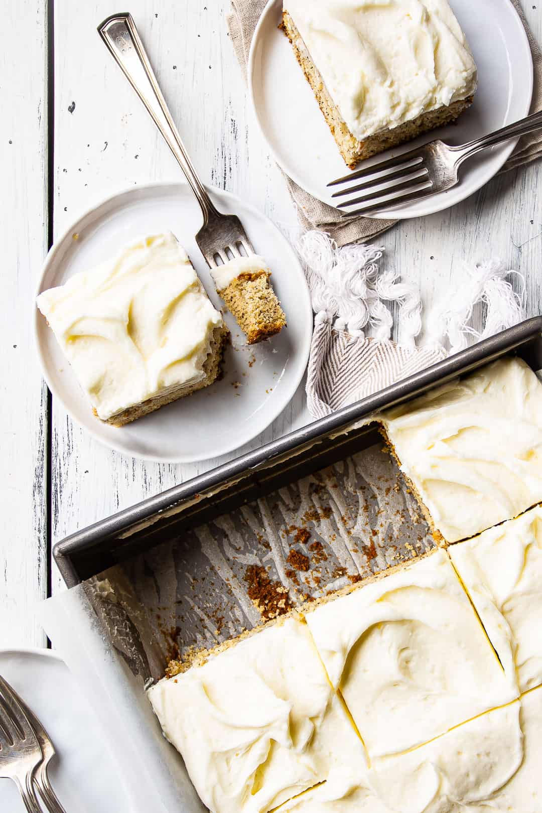 Overhead image of easy banana cake recipe, baked in a sheet pan and cut into squares.