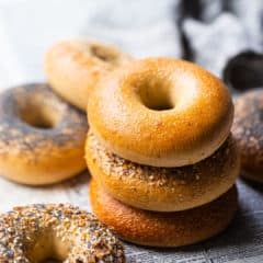 Bagel recipe, baked and served on clean newspaper, with plain, poppy seed, sesame seed, and everything bagels shown.