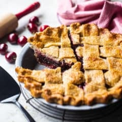 Cherry pie with a few slices cut, on a wire cooling rack with fresh cherries in the background.