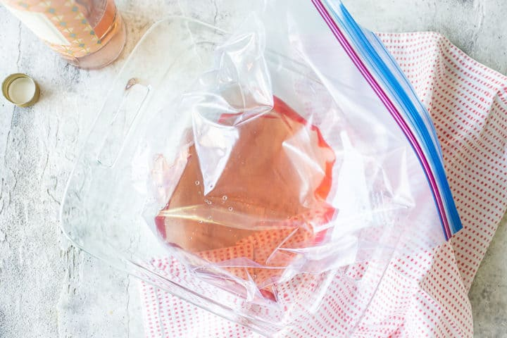 Rosé wine in a freezer bag placed in a square glass baking dish.