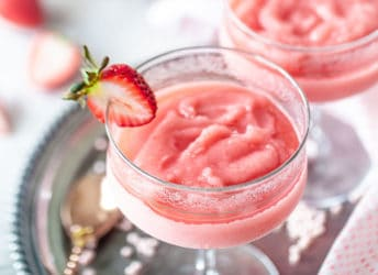 Frosé in stem glasses with strawberry garnish.
