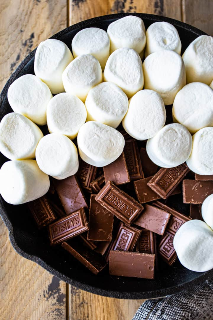 Chocolate pieces in a skillet with marshmallows layered on top.