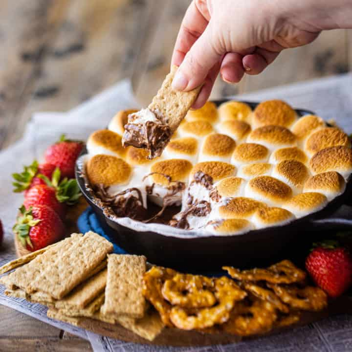 Dipping a graham cracker into s'mores dip baked in a skillet.
