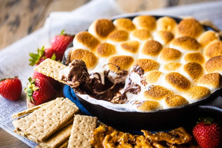 S'mores dip made in the oven with in a skillet, surrounded by various dippers.