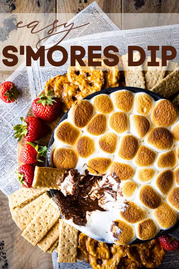 """Overhead image of s'mores dip with graham crackers, pretzels, and fresh strawberries, with a text overlay that reads """"How to Make S'mores Dip."""""""