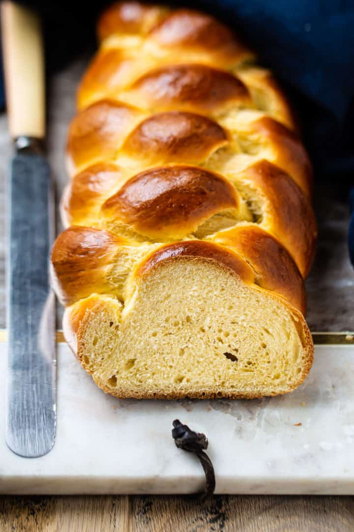 Challah recipe baked in a long braid and sliced, showing the fluffy inside of the bread.
