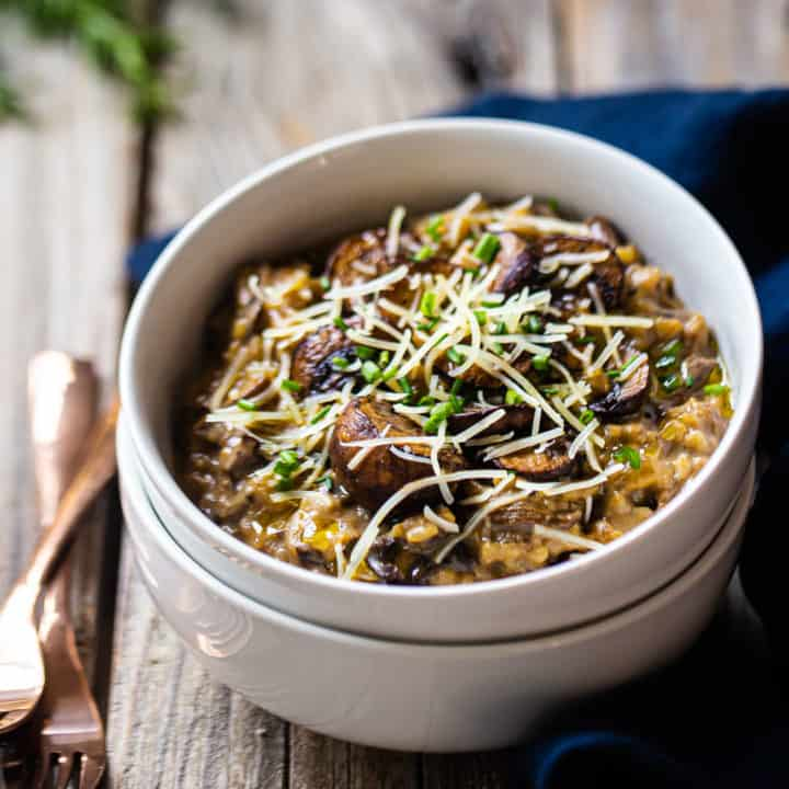 Mushroom risotto served in a white ceramic bowl with a blue linen napkin.