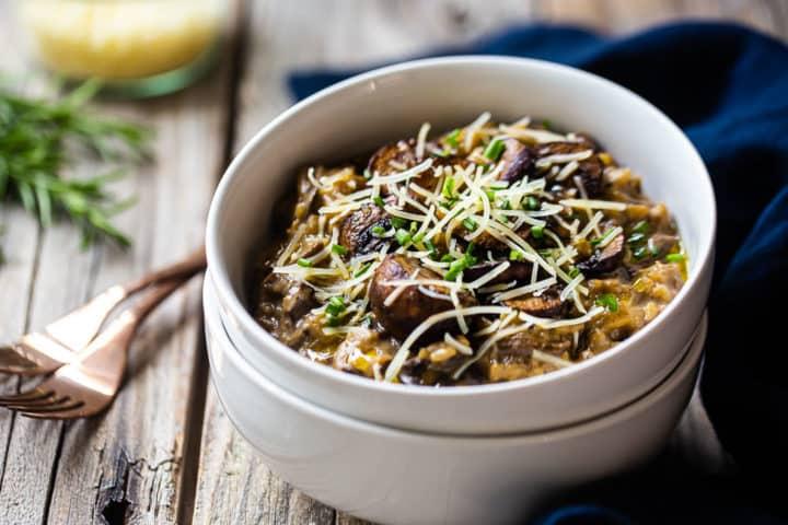 Como fazer risoto de cogumelos, com o prato acabado servido em tigelas rasas com queijo e ervas.
