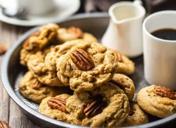 Butter pecan cookies served in a vintage pie plate with a cup of coffee and a small pitcher of cream.