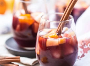 Sangria in a stemless wine glass with a cinnamon stick.