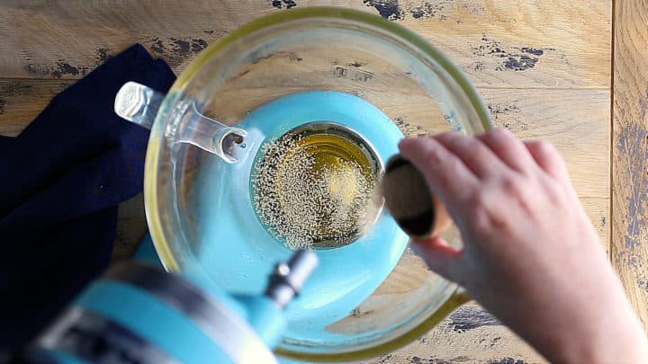 Sprinkling yeast over sweetened water.