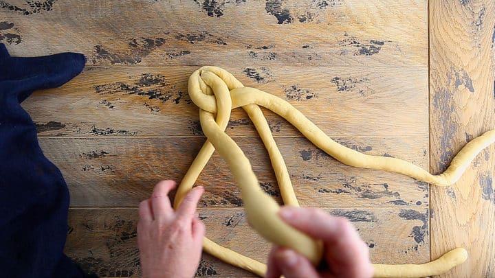 Creating a 4-strand braid with challah dough.