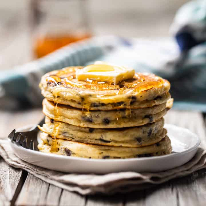 Chocolate chip pancakes with butter and syrup on a white plate.